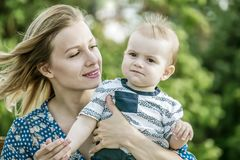 Pretty happy mather holding a baby boy outdoor on nature at sunny summer say. Emotions of love royalty free stock photos