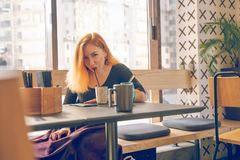 Pretty happy redheaded caucasian woman in black shirt drinks cup of coffee in the modern cafe alone. One stock image