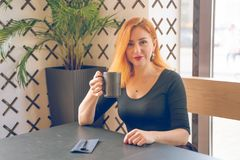 Pretty happy redheaded caucasian woman in black shirt drinks cup of coffee in the modern cafe alone. One stock photos