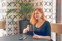 Pretty happy redheaded caucasian woman in black shirt drinks cup of coffee in the modern cafe alone. One stock photography