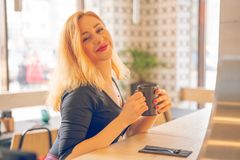 Pretty happy redheaded caucasian woman in black shirt drinks cup of coffee in the modern cafe alone stock photo