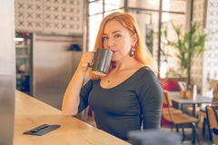 Pretty happy redheaded caucasian woman in black shirt drinks cup of coffee in the modern cafe alone stock image