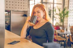 Pretty happy redheaded caucasian woman in black shirt drinks cup of coffee in the modern cafe alone. One stock images