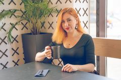 Pretty happy redheaded caucasian woman in black shirt drinks cup of coffee in the modern cafe alone. One royalty free stock photos
