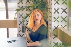 Pretty happy redheaded caucasian woman in black shirt drinks cup of coffee in the modern cafe alone. One royalty free stock photo