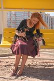 Pretty happy redheaded woman with two little dogs on the yellow summer bench. Isolated stock photo