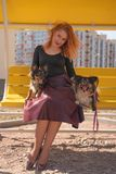 Pretty happy redheaded woman with two little dogs on the yellow summer bench. Isolated stock photography