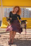 Pretty happy redheaded woman with two little dogs on the yellow summer bench. Isolated stock images