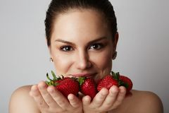 Pretty happy smiling girl with many strawberry over colorful white background.Portrait of brunette cutie with bowl of royalty free stock photo