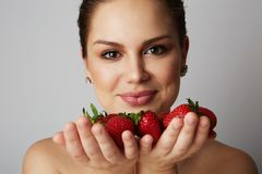 Pretty happy smiling girl with many strawberry over colorful white background.Portrait of brunette cutie with bowl of stock image
