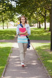 Pretty happy student carrying notebook walking Royalty Free Stock Photos