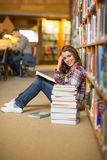 Pretty happy student reading book on library floor Royalty Free Stock Image