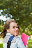 Pretty happy student smiling at camera carrying notebook Royalty Free Stock Photography