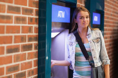 Pretty happy student withdrawing cash smiling at camera Stock Image
