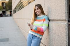 Attractive young woman on smart phone checking social media mobile apps outside city stock photos