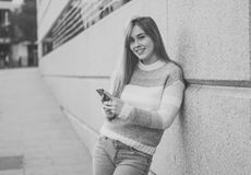 Attractive young woman on smart phone checking social media mobile apps outside city royalty free stock image