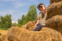 Pretty happy woman with hat leaning against the straw bales and looking away on a sunny day. Stock Photos