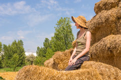 Pretty happy woman with hat sitting on straw bales and getting some rest. Royalty Free Stock Photography