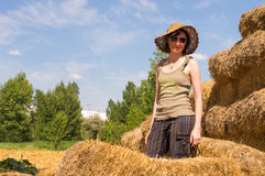 Pretty happy woman with hat standing in straw bales and looking to the camera. Stock Photo