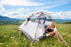 Woman tourist hiking in mountain trail, enjoying summer sunny morning in mountains near tent. Pretty happy woman hiker hiking mountain trail, sitting inside tent royalty free stock image