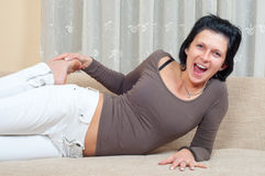 Pretty happy woman lying on the couch and laughing Stock Photos