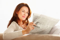 Pretty happy woman reading a newspaper Stock Photography
