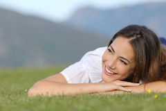 Pretty happy woman thinking on the grass and looking at side. In the mountain Royalty Free Stock Image