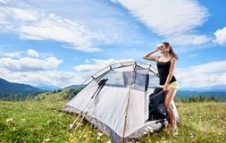 Woman tourist hiking in mountain trail, enjoying summer sunny morning in mountains near tent. Pretty happy woman tourist hiking mountain trail, standing near royalty free stock photos