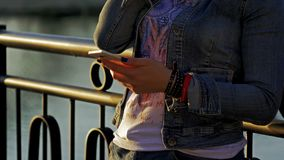 Pretty happy woman using smartphone in city park. Medium shot stock footage