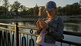 Pretty happy woman using smartphone in city park. Medium shot stock video footage