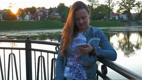 Pretty happy woman using smartphone in city park, steadicam shot. Medium Shot stock video