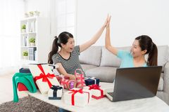 Pretty happy women using computer online shopping. At home and successful buying summer sale goods feeling cheerful looking each other giving clap Stock Images