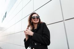 Pretty happy young hipster woman in a black elegance coat in jeans in dark fashionable sunglasses goes and laughs. Near a gray modern building in the spring day royalty free stock images