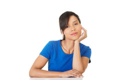 Pretty, happy, young woman in casual clothes sitting at the desk Royalty Free Stock Images