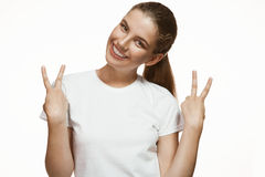 Pretty happy young woman giving peace sign Royalty Free Stock Photo