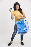 Pretty happy young woman with shopping bags and credit card. Cheerful Indian young woman with shopping bags and credit card on white Royalty Free Stock Photography