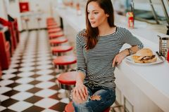 Pretty young woman sitting in the diner Royalty Free Stock Photography