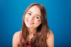 Pretty happy young woman with star shaped decoration on cheek Royalty Free Stock Images