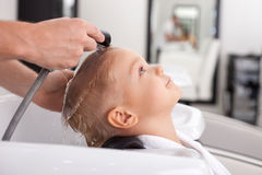 Pretty healthy boy is getting hairwash in beauty. Cheerful male child is having his hair washed in Hair salon. He is leaning his head on sink. The kid is looking Stock Photo