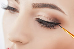 Pretty healthy girl in doing wonderful make-up. Close up of female eyes. The young woman is applying the eyeliner on her eye Royalty Free Stock Photography