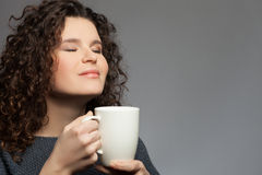 Pretty healthy woman is drinking hot coffee. Portrait of beautiful young girl enjoying a cup of tea. She is smelling the beverage and smiling. The lady closed Stock Photography