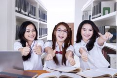 Pretty high school students giving thumbs up. Three pretty high school students giving thumbs up at the camera while studying together in the library Stock Image