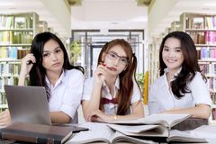 Pretty high school students sit in library Stock Photo