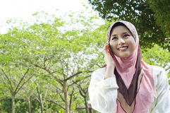 Pretty hijab women use a cellphone. Pretty muslim woman use a cellphone at park Royalty Free Stock Image