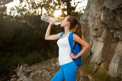 Pretty hiker girl drinking water. Shapely woman tourist with backpack drinking water in nature. Caucasian female drinks Stock Image
