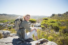 Pretty hiker sitting at the summit smiling at camera Royalty Free Stock Photo