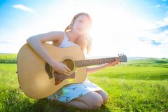 Pretty hippie girl playing acoustic guitar and singing songs. Talented girl relaxing at green spring or summer meadow Royalty Free Stock Photography