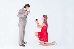 Pretty hipster on bended knee doing a marriage proposal to her boyfriend. On white background Stock Image