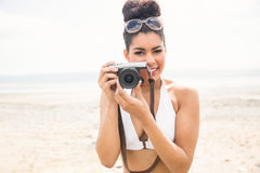 Pretty hipster in bikini taking picture Royalty Free Stock Photography