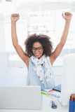 Pretty hipster cheering at her desk with laptop Royalty Free Stock Images